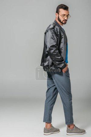 Photo pour Modèle masculin à la mode en tenue d'automne posant sur fond gris - image libre de droit