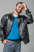 smiling male model in stylish black bomber posing with hand in pocket isolated on grey background