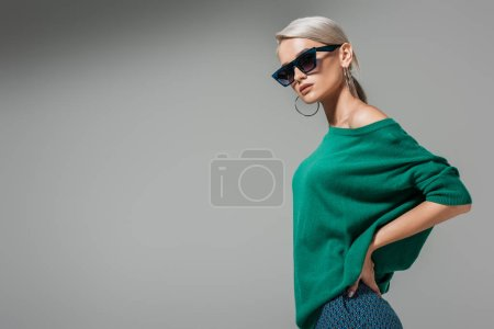 Photo for Fashionable young woman in sunglasses posing with hands on waist isolated on grey background - Royalty Free Image