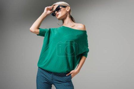 Foto de Hermosa mujer modelo en gafas de sol y suéter verde posando aislada sobre fondo gris - Imagen libre de derechos