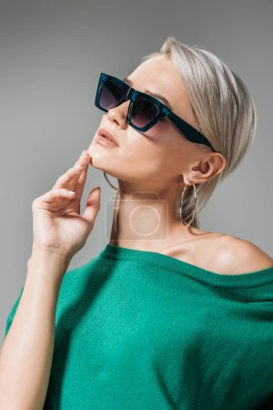 stylish woman in sunglasses and green sweater posing with hand on chin isolated on grey background