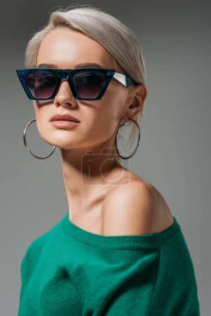 attractive female model in sunglasses and green sweater looking at camera isolated on grey background