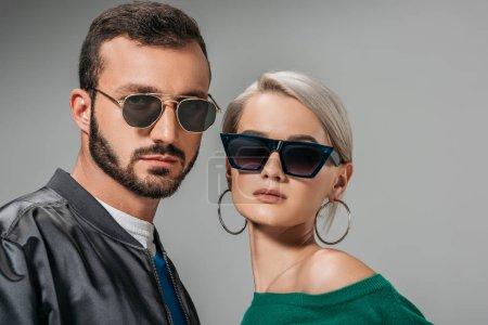 Photo pour Couple à la mode posant dans des lunettes de soleil à la mode, isolé sur gris - image libre de droit