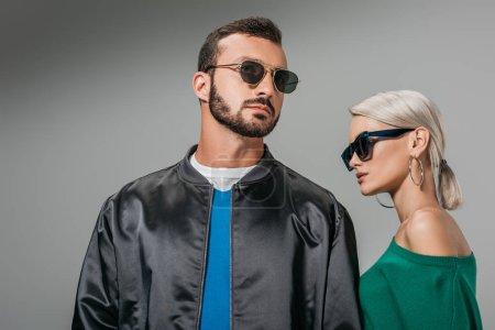 Photo pour Couple à la mode posant dans des lunettes de soleil, isolé sur gris - image libre de droit