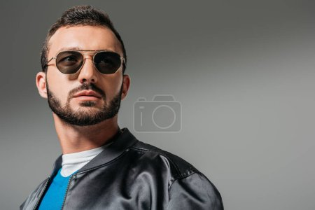 bearded man posing in black bomber and sunglasses,  isolated on grey