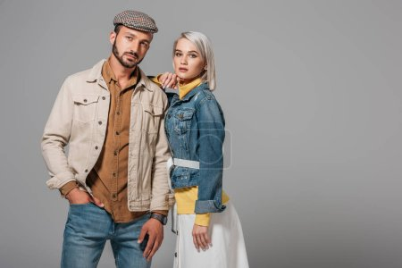 Photo for Beautiful couple of models posing in autumn outfit, isolated on grey - Royalty Free Image