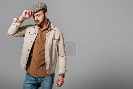 bearded stylish man posing in autumn jacket and tweed cap, isolated on grey
