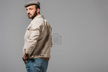 bearded handsome man in autumn jacket and tweed cap, isolated on grey