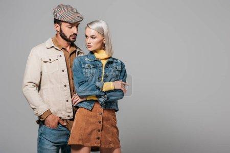 elegant stylish couple posing in autumn outfit, isolated on grey