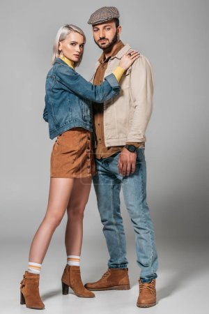 beautiful couple posing in stylish autumn outfit, on grey
