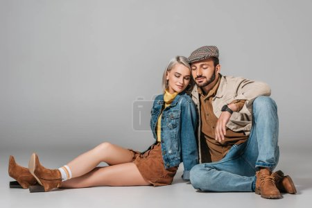 happy couple in autumn outfit sitting on floor, on grey