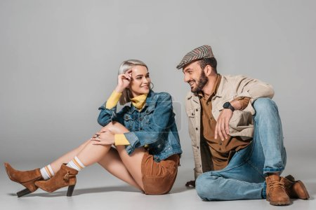 stylish couple sitting in autumn outfit and looking at each other, on grey