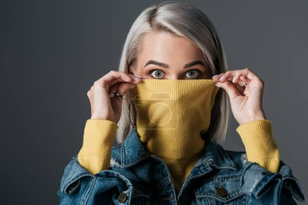 shocked woman in yellow turtleneck and jeans jacket, isolated on grey