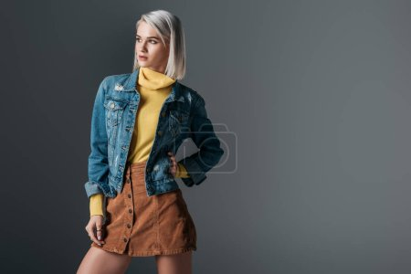 attractive woman posing in yellow turtleneck, trendy corduroy skirt and jeans jacket, isolated on grey