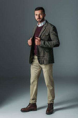 handsome male model posing in beige pants and tweed jacket, on grey