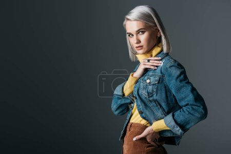 Photo for Attractive girl in yellow turtleneck and fashionable jeans jacket, isolated on grey - Royalty Free Image