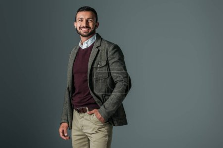 handsome smiling man posing in tweed jacket, isolated on grey