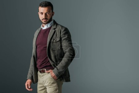 handsome bearded man posing in autumn tweed jacket, isolated on grey