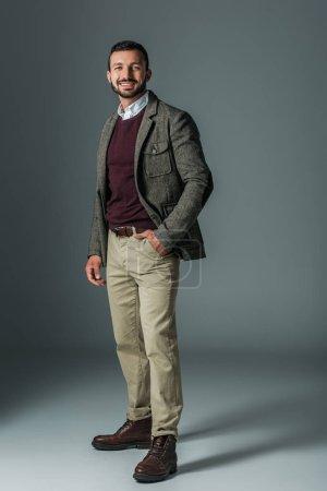 elegant male model posing in beige pants and tweed jacket, on grey