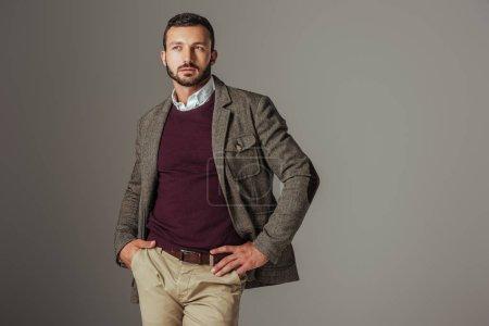 elegant stylish man posing in autumn tweed jacket, isolated on grey
