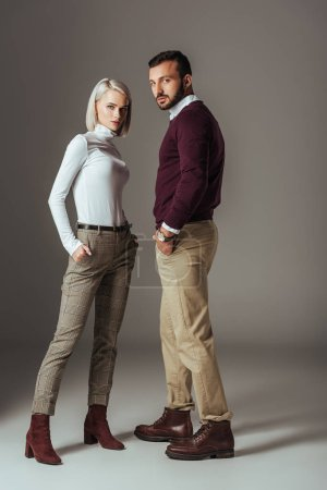 couple of models posing in stylish autumn outfit, on grey