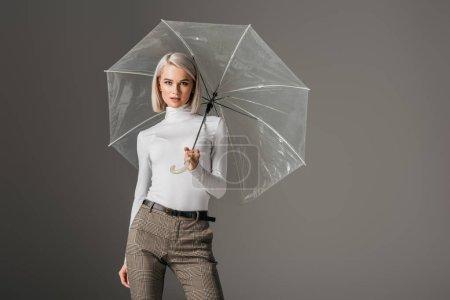 elegant model in white turtleneck with transparent umbrella, isolated on grey