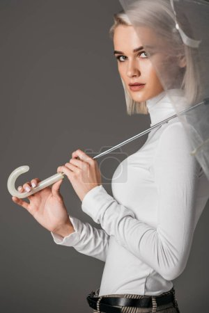 elegant girl in white turtleneck posing with trendy transparent umbrella, isolated on grey