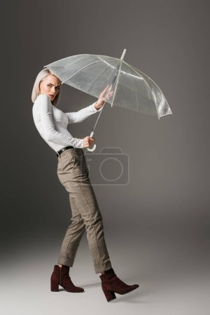 confused girl in white turtleneck with transparent umbrella, on grey