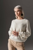 attractive girl posing in white autumn sweater and round earrings, isolated on grey