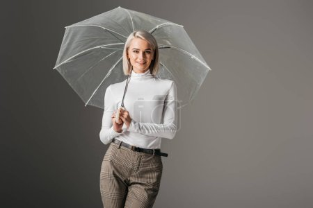 beautiful girl in white turtleneck posing with transparent umbrella, isolated on grey
