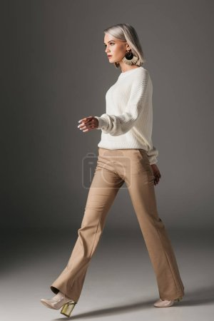 fashionable girl walking in beige pants and white sweater, on grey