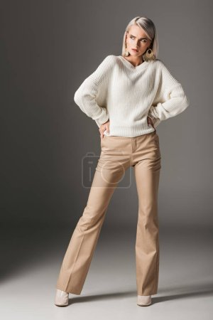 attractive elegant girl posing in white sweater and beige pants, on grey