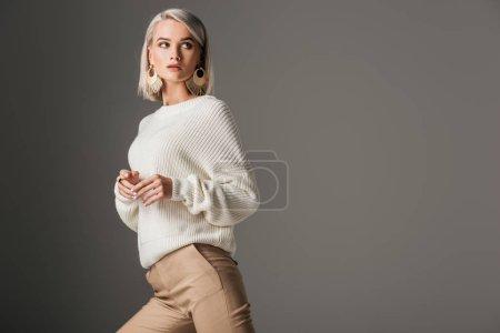 Foto de Elegante modelo rubio posando en suéter de punto blanco, aislado en gris - Imagen libre de derechos