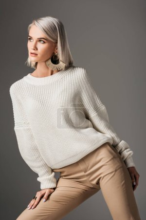 attractive elegant woman posing in white autumn sweater, isolated on grey