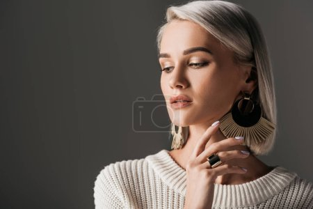 Photo for Elegant girl posing in white knitted sweater and round earrings, isolated on grey - Royalty Free Image