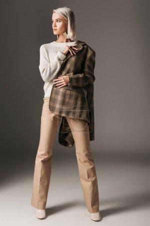 Photo pour Élégant modèle élégant posant en pull d'automne, pantalon beige et veste en tweed, sur gris - image libre de droit