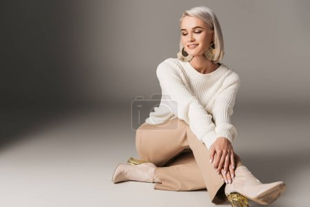 Photo for Smiling elegant model posing in white sweater, beige pants and autumn heels, on grey - Royalty Free Image