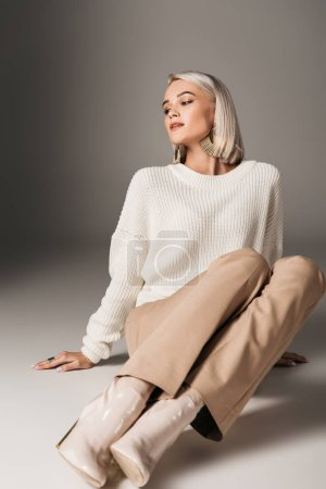 fashionable beautiful girl posing in white sweater, beige pants and trendy autumn heels, on grey