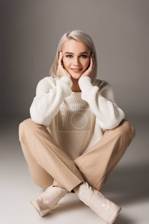 beautiful girl sitting in white sweater and beige pants, on grey