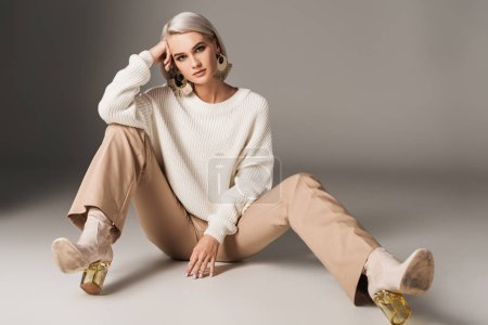 fashionable model posing in white sweater, beige pants and autumn heels, on grey