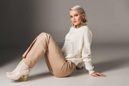 stylish beautiful girl posing in white sweater and autumn heels, on grey