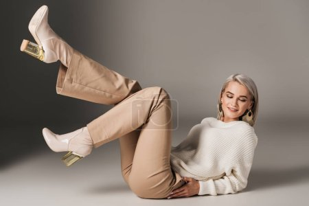 fashionable girl posing in white sweater and autumn heels, on grey
