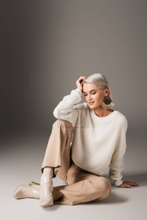 attractive model posing in white sweater, beige pants and autumn heels, on grey