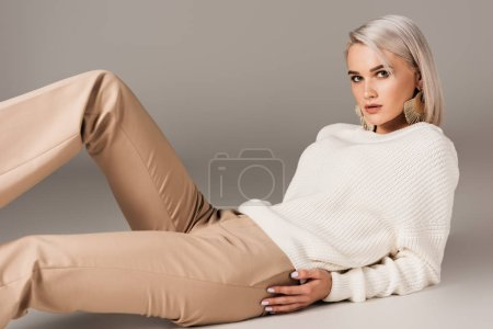 Photo for Elegant blonde woman lying in white sweater and beige pants, on grey - Royalty Free Image