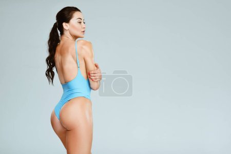 back view of sexy sportive woman in blue swimwear isolated on grey