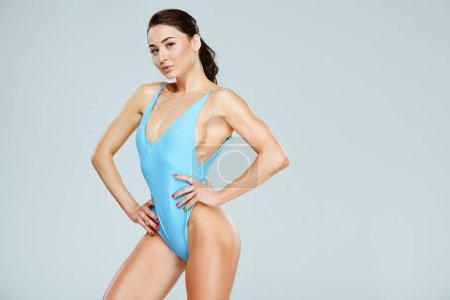 Photo pour Sexy sportive femme posant en maillot de bain bleu isolé sur gris - image libre de droit