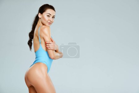 side view of seductive sportive woman in blue leotard standing with crossed arms isolated on grey