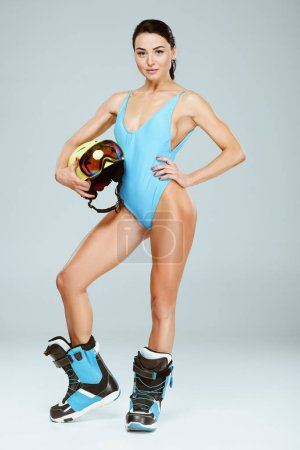 sexy sportswoman in blue swimwear holding helmet and ski goggles isolated on grey