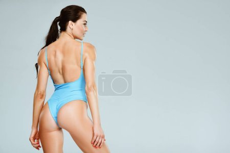 back view of sexy sportive woman in blue swimwear looking away isolated on grey