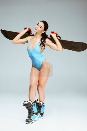 sexy sportswoman in blue sportswear holding snowboard on shoulders isolated on grey